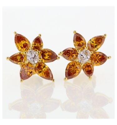 Rionore flower shaped stud earrings featuring two tone diamonds set in gold.